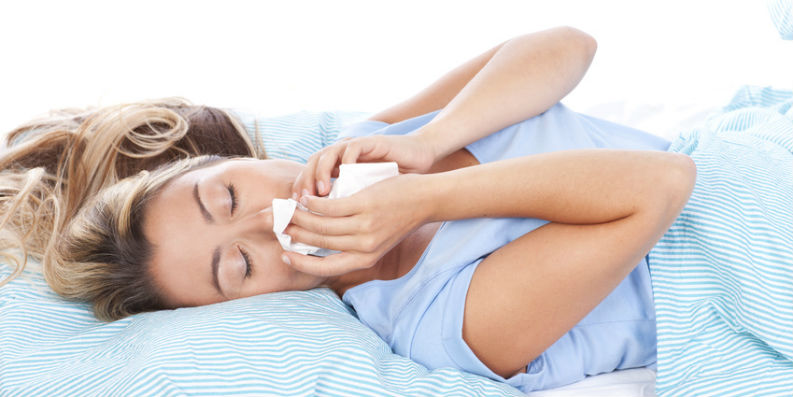 Frau liegt in Bett und hält sich ein Taschentuch an die Nase