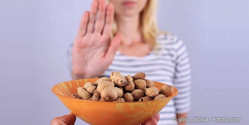 Frau lehnt Schüssel mit Erdnüssen ab
