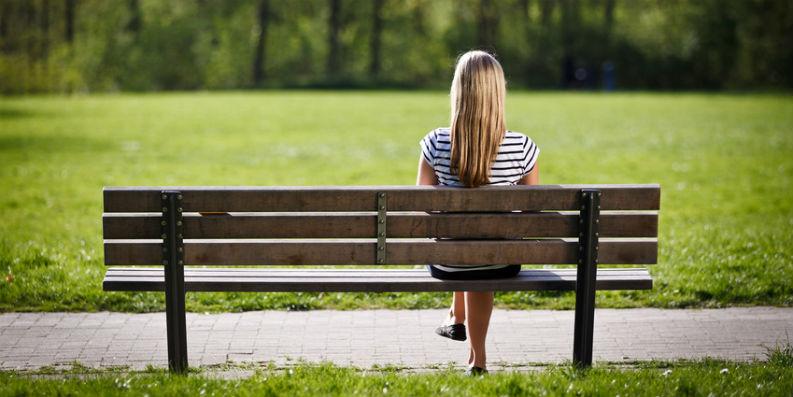 Frau sitzt mit Rücken zur Kamera auf einer Parkbank