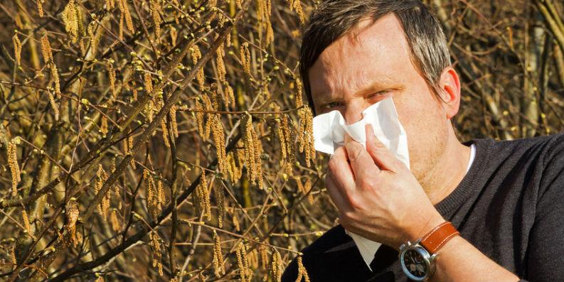 Mann putzt sich die Nase